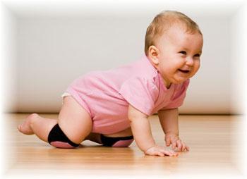 Малыш ползет по полу, пытаясь встать
