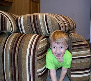Ребенок играет диванными подушками
