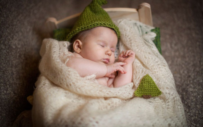 Новорожденный спит в кроватке